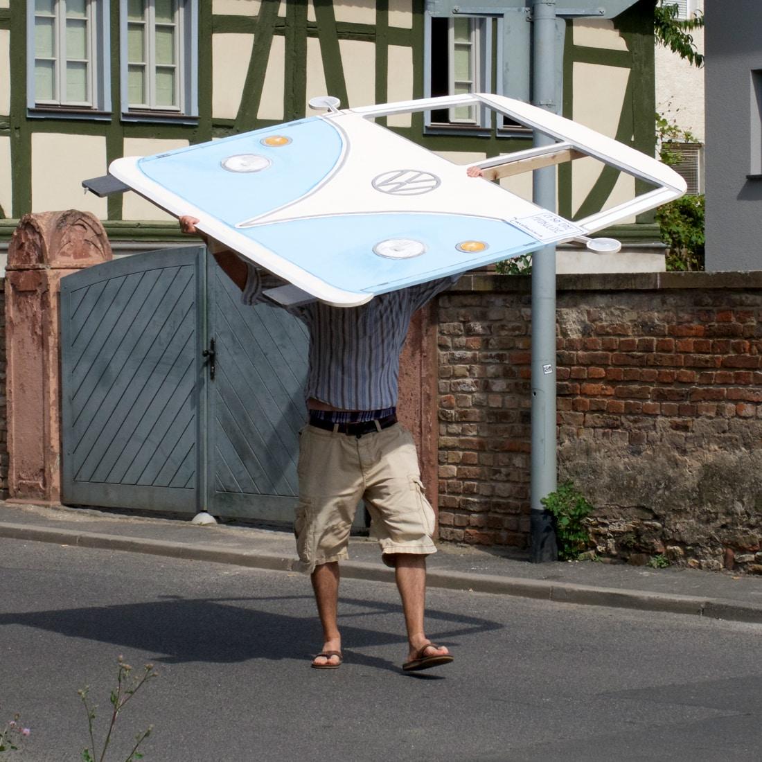 Ein Mann trägt eine Kulisse eines Bulli T1