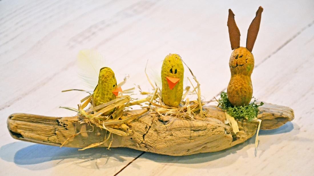 Drei aus Erdnüssen gebastelte Küken und ein Huhn sitzen auf einem Ast