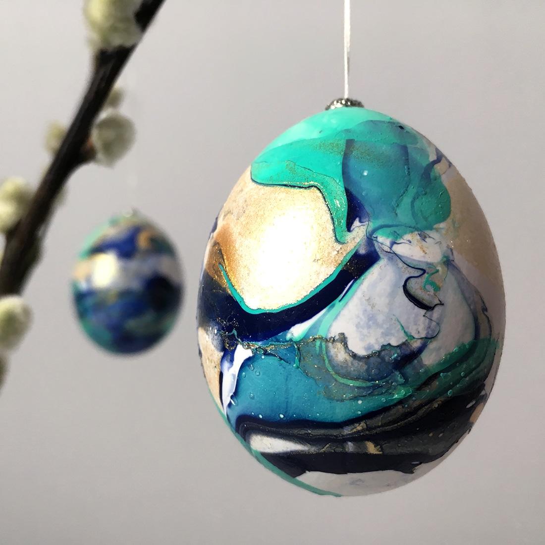 Zwei mit Nagellack marmorierte Eier an Weidenkaetzchen