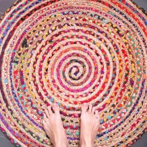 Nackte Füße auf kunterbuntem Teppich