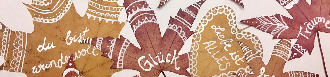 Bemalte Blätter liegen nebeneinander
