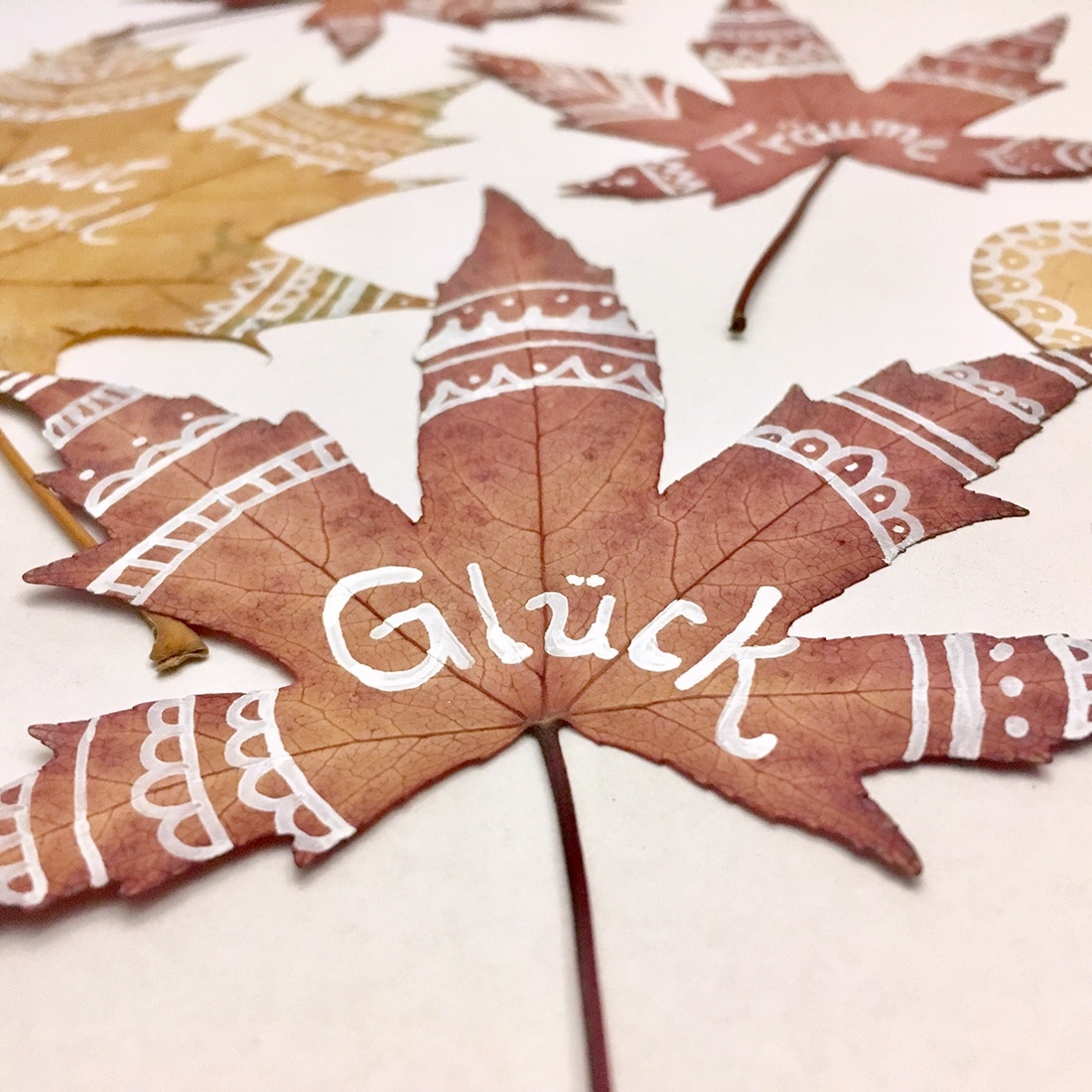 Glück - Mit Mandala-Mustern bemalte Blätter